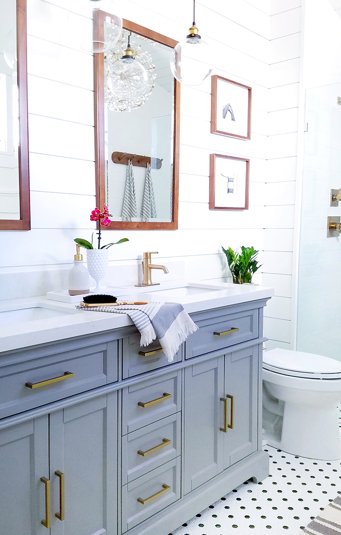 gray vanity and wooden mirrors in bath