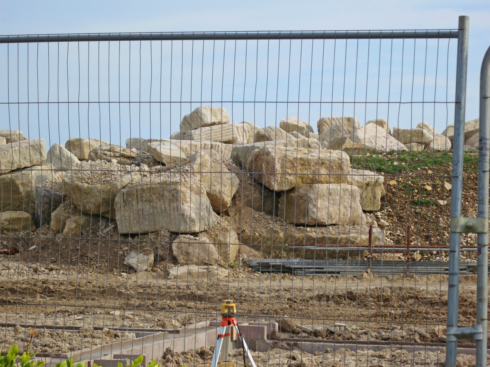 Huge, hewn rocks of Portland stone behind a fence with theodolite in foreground.