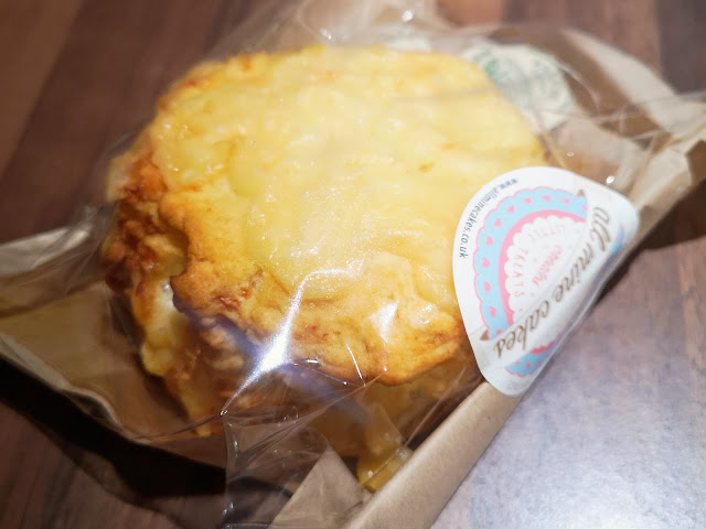 Image shows a close up image of a packaged cheese scone with a label that reads all mine cakes by the lake.