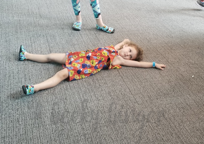 A toddler in an orange floral dress, laying on the floor during a tantrum