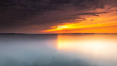 Screen background with serene views, sunset, skyline, sea, clouds.