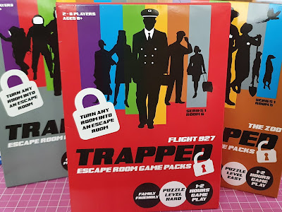 3 closed Trapped Family Escape Room Game Packs on table