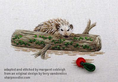 Needlepainted hedgehog peeking over needlepainted log at a stumpwork detached red berry and leaf. (Stumpwork and thread painted hedgehog)