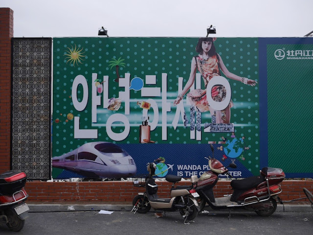 "Wanda Plaza ""안녕하세요"" sign on a wall bordering a construction site in Mudanjiang, China"