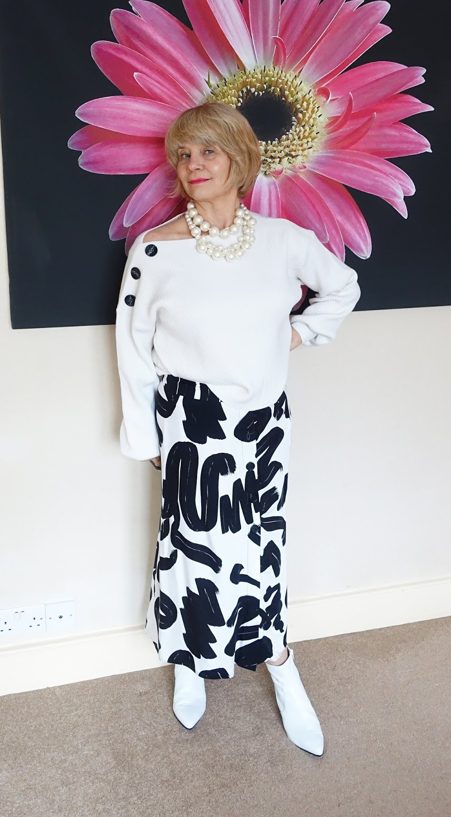 An abstract patterned white and black midi skirt worn with an ivory jumper and white ankle boots. A contemporary look for a woman of any age