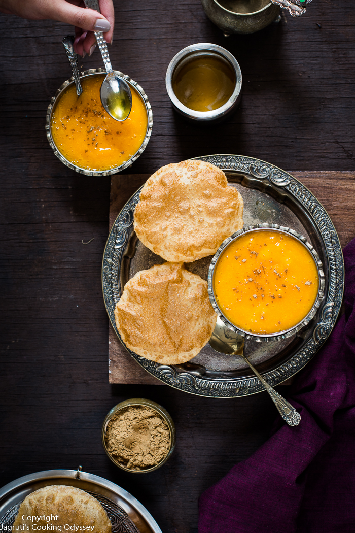 Indian style mango pulp served in two metal bowl, served with ghee and ginger powder on top with poori on a metal tray.