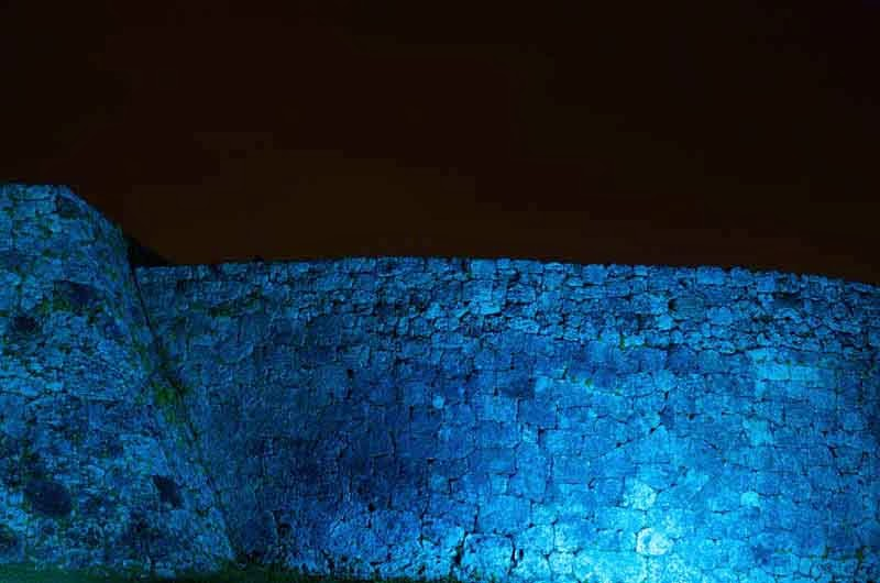 stone castle walls, illuminated at night