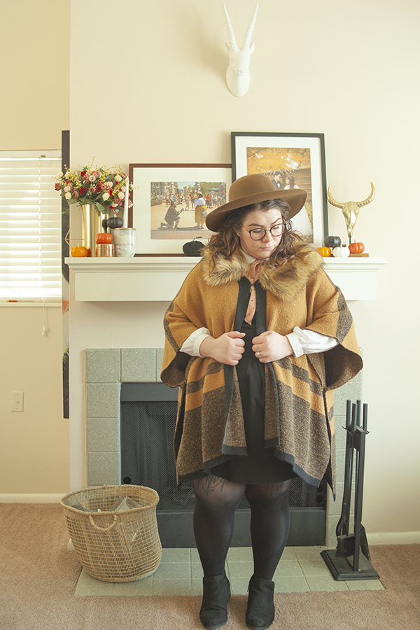 An outfit consisting of a brown wide brim hat, white Peter Pan collar blouse under a black pinafore dress with a brown and black faux fur trimmed poncho with tights and ankle boots.