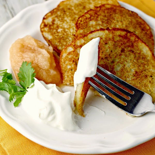 A piece of Easy Potato Pancakes by Renee's Kitchen Adventures on a fork with sour cream. Applesauce and sour cream on plate with pancakes in background.