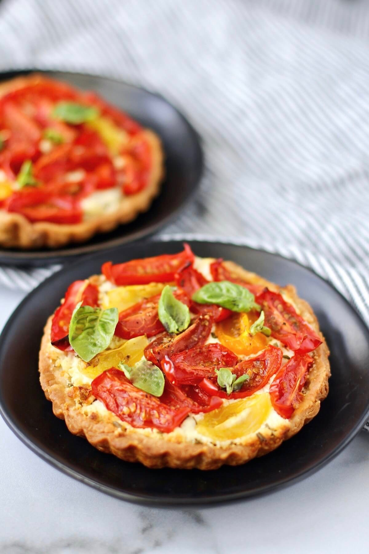 Tomato, basil, and goat cheese tarts on plates.