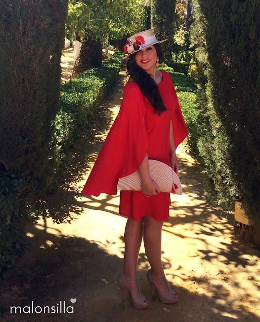 Chica con vestido rojo con capa, de pie en unos jardines, con canotier y bolso malonsilla
