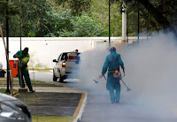 A truck sprays insecticide near grounds workers at Olympic media accommodations as part of preventative measures against the Zika virus and other mosquito-borne diseases in Rio de Janiero, Brazil. (Credit: Reuters/Chris Helgren) Click to Enlarge.