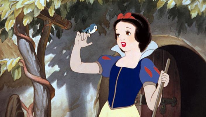 Imagem: a personagem Branca de Neve, uma jovem princesa com a pele branca, os cabelos pretos e lábios vermelhos, um vestido azul com uma saia amarela, segurando uma vassoura em uma mão e na outra um passarinho e atrás a casa dos sete anões com uma árvore crescendo ao lado.