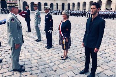 L'illustration représente une photo du compte instagram des Pompiers de Paris sur laquelle on voit Pierre Niney en garde à vous dans la cour des invalides lors de sa remise de grade de première classe honorifique.