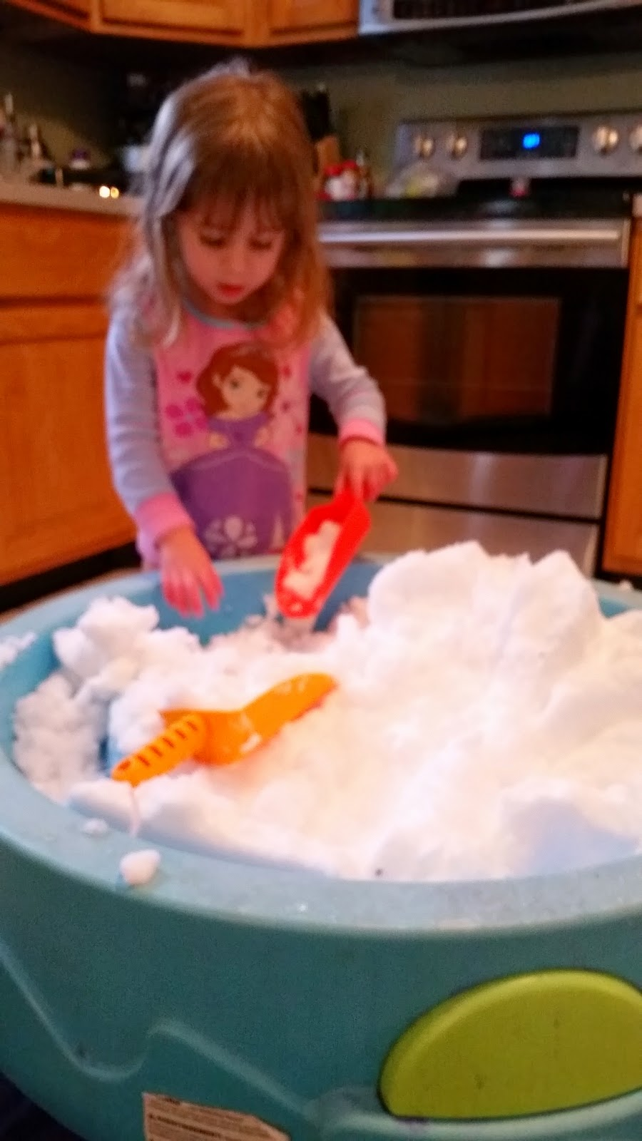 toddler playing with snow inside using the water table