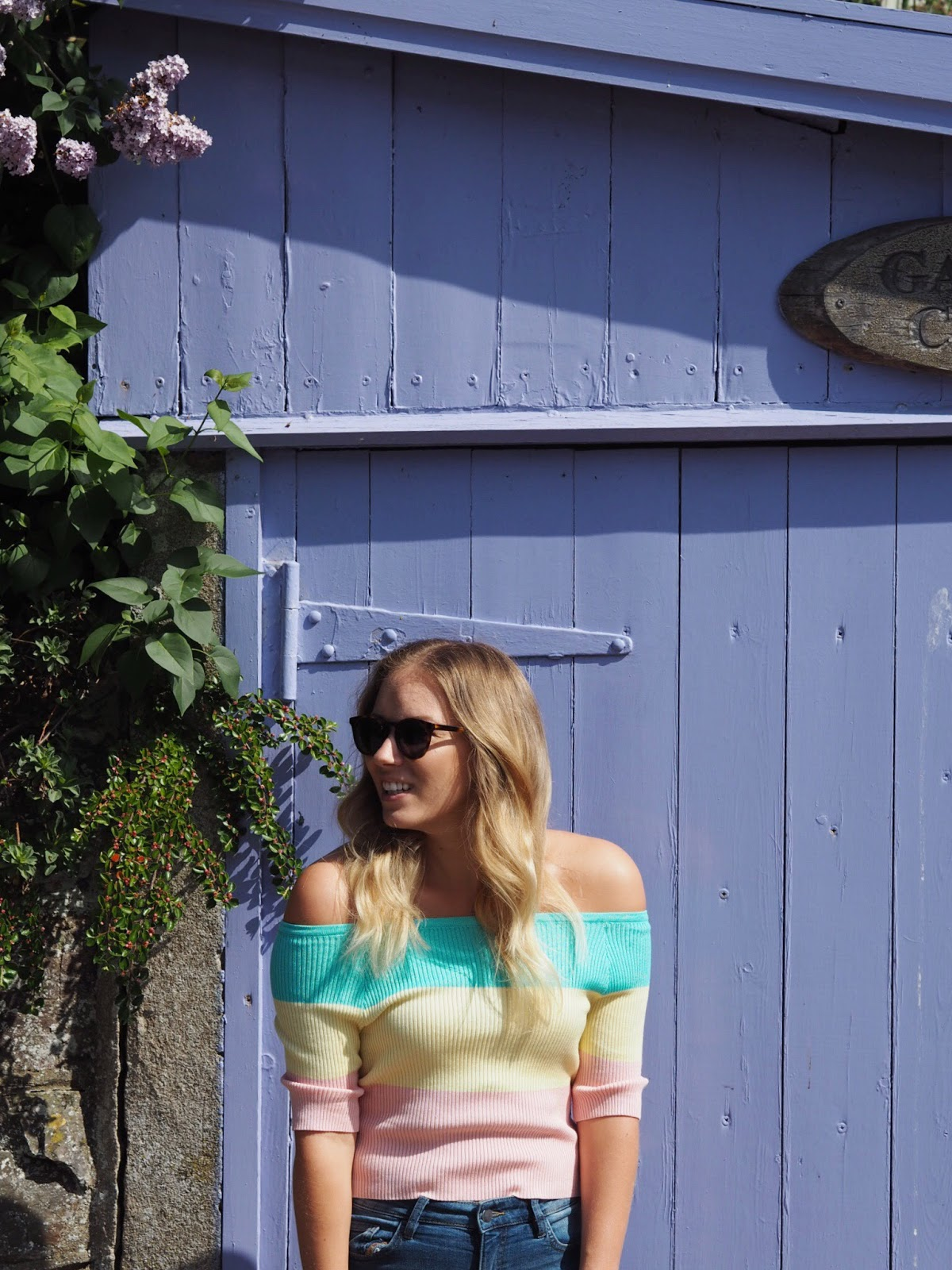 Rachel Emily Wearing a pastel stripe bardot top in mint, yellow and pink with denim shorts in front of a lilac garage