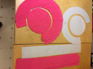 Pattern pieces for hat and pieces cut from pink fleece.