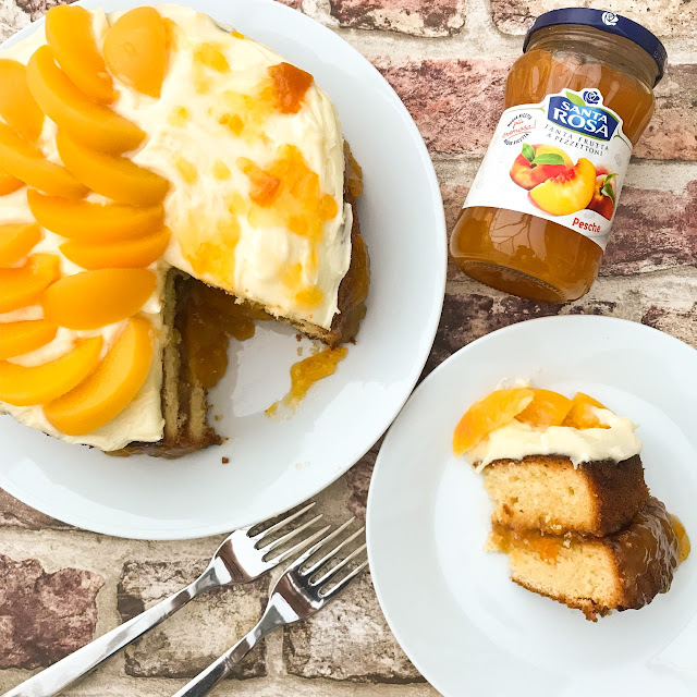Completed cake topped with icing, peaches and jam drizzle, with a piece cut and on a separate plate, with two forks placed nearby and a jar of the Santa Rosa Conserve