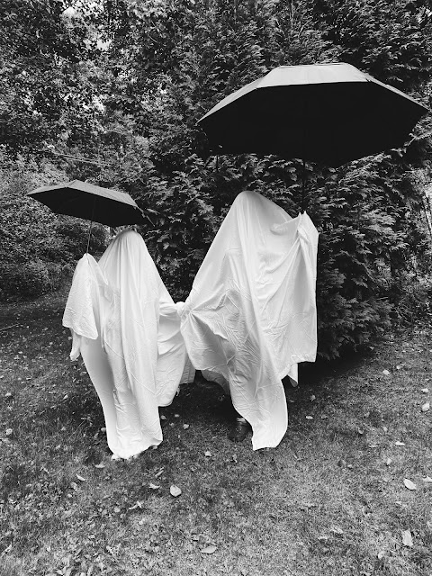 Black and white photo of two bedsheet ghosts, one tall and one small, holding black umbrellas