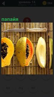 На столе лежит папайя и рядом нож, которым разрезан плод попалам