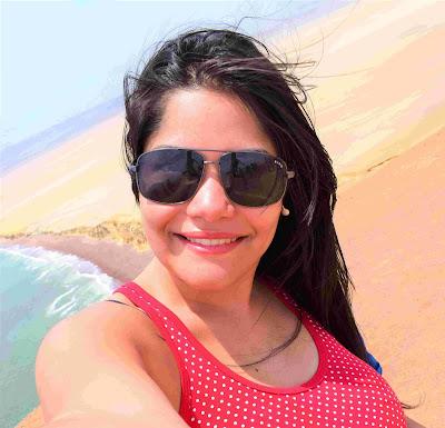 selfie de mulher jovem com oculos escuros, blusa vermelha com bolinhas brancas