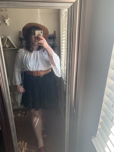A mirror selfie of an outfit of a brown panama hat, white off the shoulder blouse, black pleated skirt and brown slide sandals.