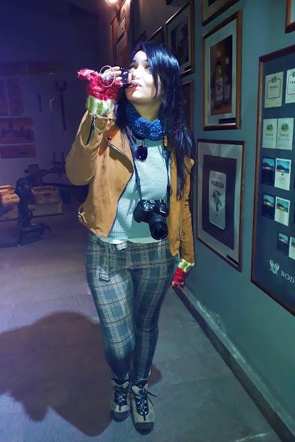 mulher jovem de cabelo preto, pele branca. Vestida de jaqueta de camurça marron e luvas vermelhas em uma vinicola