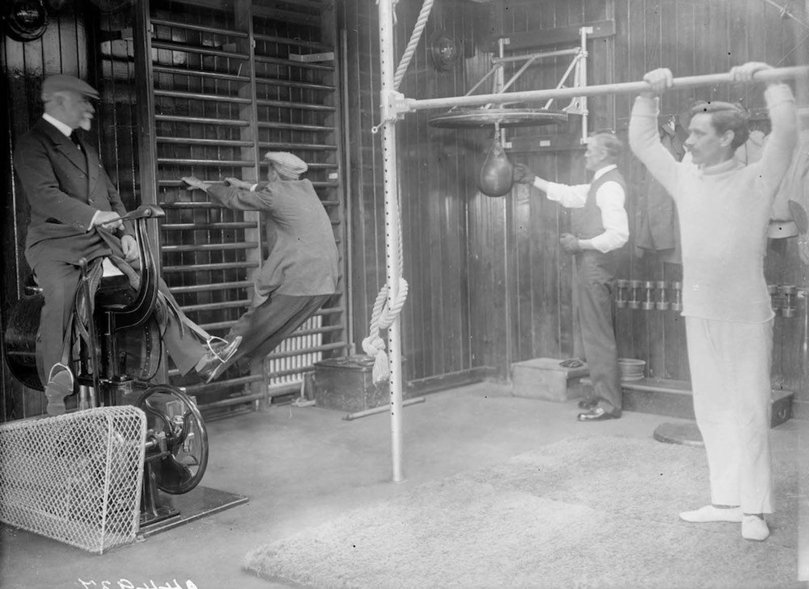 Passengers working out in the gym of the Cunard cruise liner Franconia, which was destroyed by a U-boat in 1916. Amongst the equipment is a punchbag and an early cycling machine. 1912.
