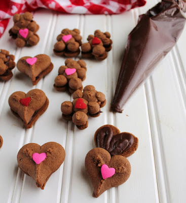 chocolate teddy bear and heart cookies being filled with piping bag full of dark chocolate ganache frosting