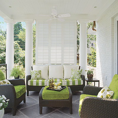 Lime green and dark wicker furniture look amazing on this white shuttered front porch