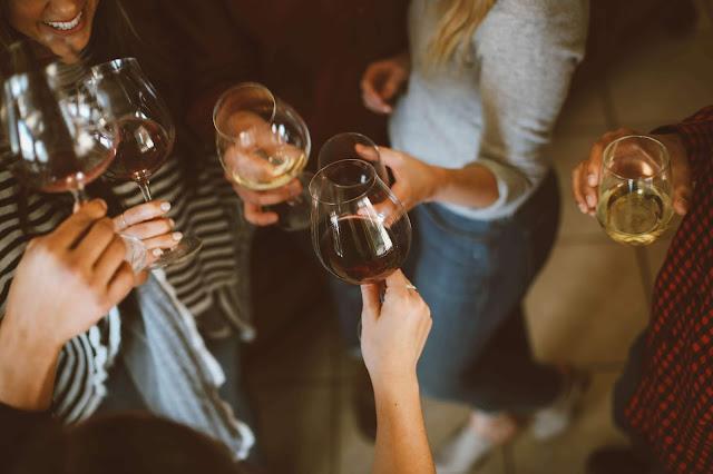 ludzie z kieliszkami białego i czerwonego wina w ręku