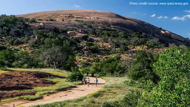 a trio of hikers walking down the path away from Enchanted Rock