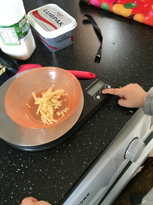 toddlers finger pressing button on digital scale with bowl of cheese on scale