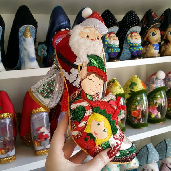 festive shoe in hand with snowglobe heel and shoe shelves in background