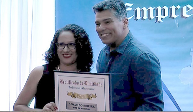 """Elizandra Aparecida Nóbrega do site """"O Vale do Ribeira"""", recebendo do ator Mauricio Mattar o prêmio de melhor site da região pelo oitavo ano consecutivo."""