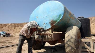 Un palestino bebe de un depósito de agua potable.