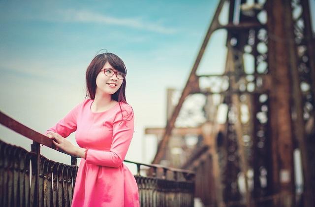 woman in pink dress with red eyewear on the bridge