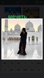 девушка стоит в помещении на фоне мечети белого цвета