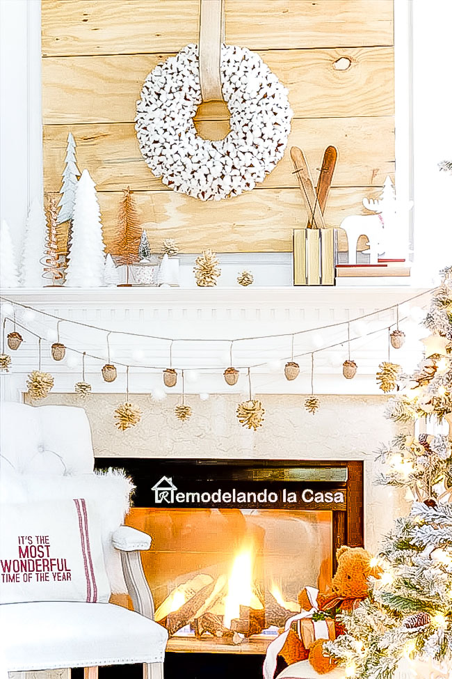 Rustic Christmas mantel with wooden tones and pine garlands