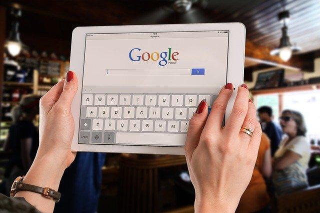 tangan cantik dari wanita yang sedang memegang ipad nya untuk melakukan pencarian pada Google