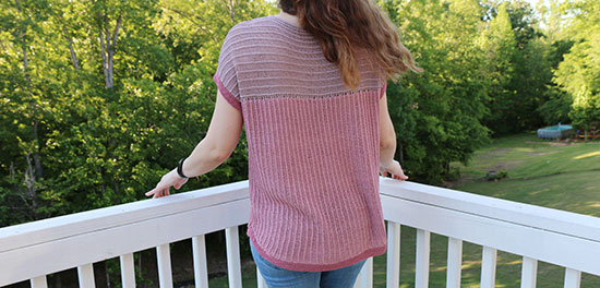 Back view of a woman standing outside wearing a hand knit short sleeve top in shades of pink.