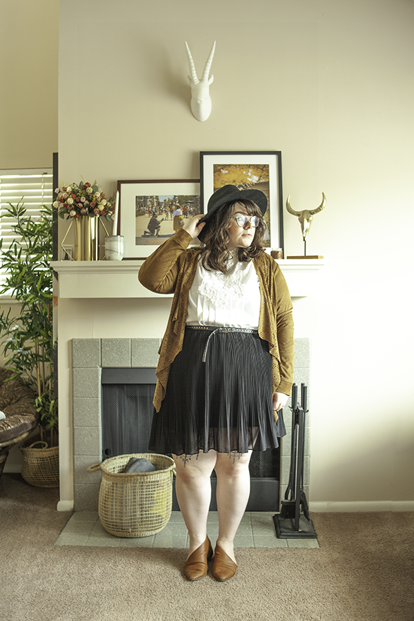 An outfit consisting of a black wide brim fedora, a brown suede laser cut shawl jacket, a white vintage blouse with lace lib detailing, black pleated skirt and brown d'orsay flats.