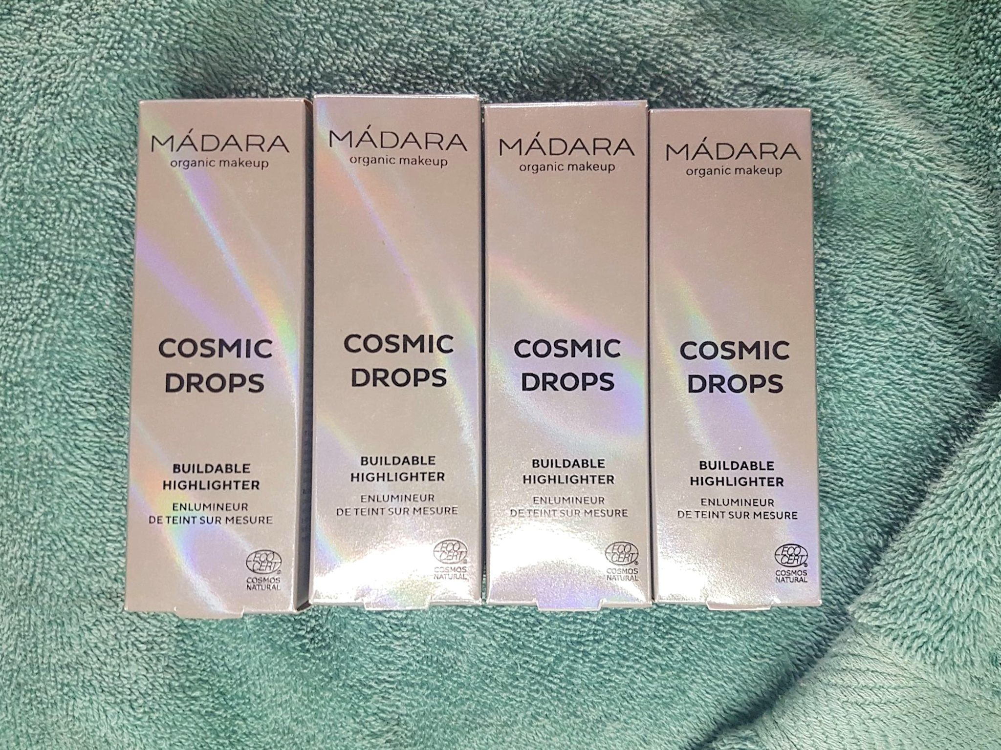 rainbow holographic packaging from Madara, four shades of Cosmic Drops from the natural liquid highlighter range on a teal terrycloth towel