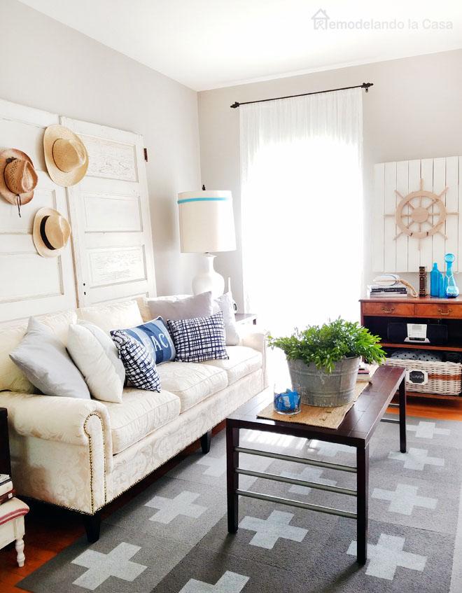 DIY Swiss cross rug, ship wheel art, beach pillow, vintage bucket on coffee table