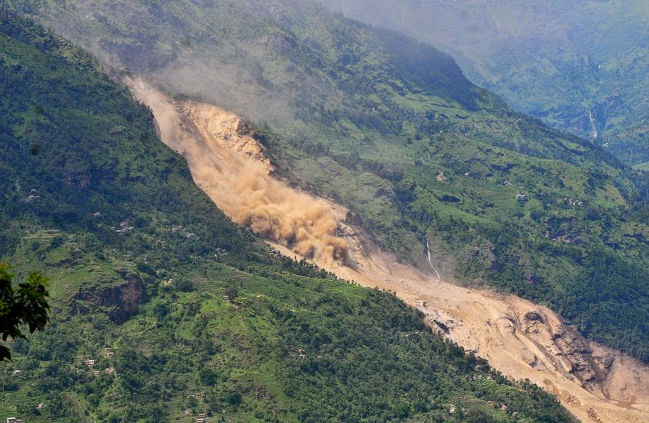 A cloud of dust rises as loose earth moves down a slope at the site of a landslide in Sindhupalchowk area, about 120 kilometers (75 miles) east of Katmandu, Nepal, Saturday, Aug. 2, 2014. A massive landslide killed at least eight people and blocked a mountain river in northern Nepal on Saturday, causing the water to form a lake that was threatening to burst and sweep several villages, officials said.