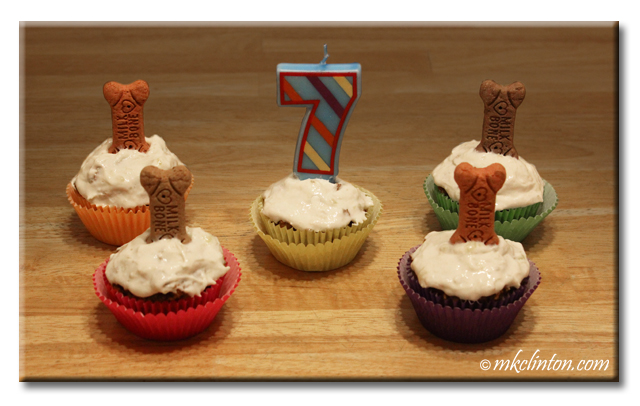 five pupcakes with bone treats sticking out of them and a 7 candle