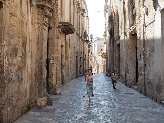 Niños corriendo en una calle en Lecce
