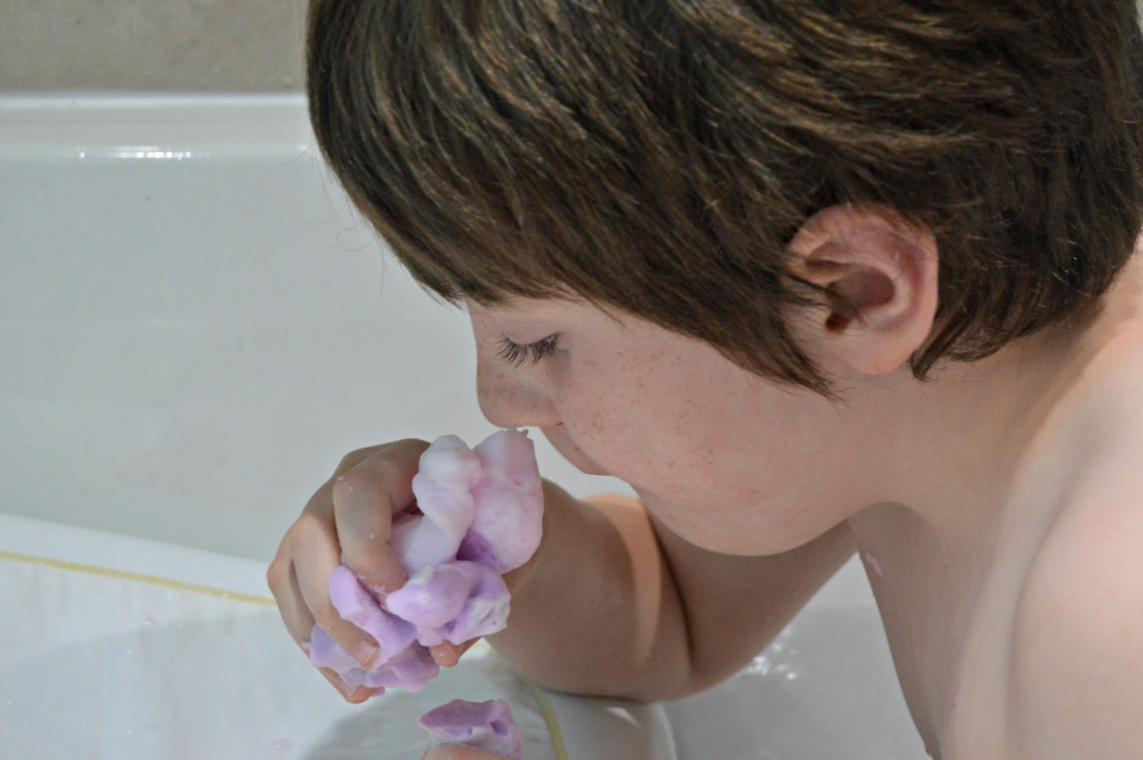 boy in the bath smelling soap
