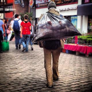 Hambriento Juan camina a la cafetería de  la multinacional donde solía ir cuando  tenía crédito y dinero con la esperanza de  que el calor humano le ayudará a calmar  su hambre. Con suerte alguien tendrá la  humanidad de invitarlo a un café.