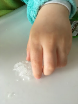 close up of toddlers hand trying to pick up hail on highchair tray